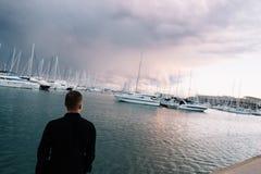 Un uomo vicino agli yacht bianchi sull'acqua Barche sull'acqua dell'oceano Un yacht bianco I rami dell'albero Bello Immagine Stock Libera da Diritti