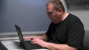 Un uomo vicino alla finestra di un treno commovente lavora con un computer portatile video d archivio