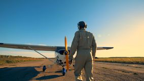 Un uomo viene ad un biplano, esaminando la sue elica ed ali 4K video d archivio