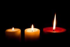 Un'ustione da tre candele nello scuro Immagine Stock