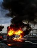 Un véhicule retourné en flammes photographie stock