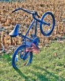 Un vélo bleu se penchant vers l'arrière par lui-même avec un drapeau dans les rais dans un domaine Images libres de droits