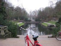 Un vélo rouge garé devant un lac en parc de Muziekkoepel Noorderplantsoen à Groningue, Pays-Bas photo stock