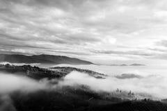 Un valle en otoño llenó por la niebla en la puesta del sol, de las colinas emergentes Imágenes de archivo libres de regalías