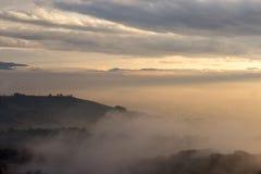 Un valle en otoño llenó por la niebla en la puesta del sol, de las colinas emergentes Imagen de archivo libre de regalías