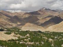 Un valle enorme de la montaña: las montañas marrones, sombras en las cuestas, abajo en la parte ancha del valle son muchos árbole Imágenes de archivo libres de regalías