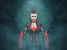 Un vampiro de la señora joven que presenta en un vestido de Halloween Fotos de archivo libres de regalías