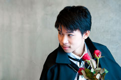 Un vampiro del adolescente con las rosas rojas Foto de archivo