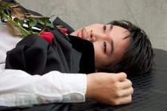 Un vampiro del adolescente con las rosas rojas Foto de archivo libre de regalías