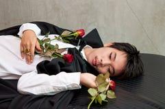 Un vampiro del adolescente con las rosas rojas Imagenes de archivo