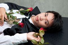 Un vampiro del adolescente con las rosas rojas Fotos de archivo libres de regalías