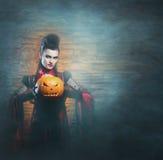 Un vampiro ledy joven y atractivo que lleva a cabo un pupmpkin Imagenes de archivo