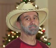 Un vaquero barbudo por un árbol de navidad Imagen de archivo
