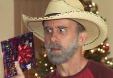 Un vaquero barbudo Tries para conjeturar su regalo de Navidad Imagenes de archivo