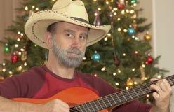 Un vaquero con una guitarra por un árbol de navidad Imágenes de archivo libres de regalías