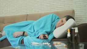 Un varón adulto con mentiras frías de los síntomas envuelto en una manta en el sofá y los canales de televisión de los interrupto almacen de metraje de vídeo