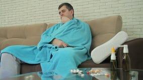 Un varón adulto con síntomas fríos se sienta envuelto en una manta en el sofá, temperatura del cuerpo de las medidas y cambia la  metrajes