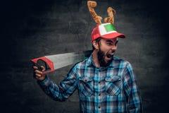 Un varón barbudo en un sombrero con los cuernos del ` s de los ciervos sostiene el handsaw Imagen de archivo