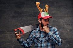 Un varón barbudo en un sombrero con los cuernos del ` s de los ciervos sostiene el handsaw Fotografía de archivo