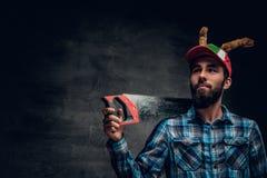 Un varón barbudo en un sombrero con los cuernos del ` s de los ciervos sostiene el handsaw Foto de archivo
