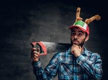 Un varón barbudo en un sombrero con los cuernos del ` s de los ciervos sostiene el handsaw Fotos de archivo
