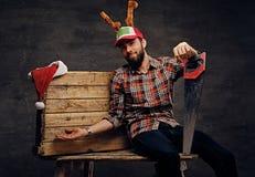 Un varón barbudo en sombrero de la Navidad con los cuernos del ` s de los ciervos sostiene el handsaw Imagenes de archivo