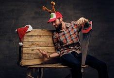 Un varón barbudo en sombrero de la Navidad con los cuernos del ` s de los ciervos sostiene el handsaw Foto de archivo libre de regalías