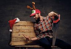Un varón barbudo en sombrero de la Navidad con los cuernos del ` s de los ciervos sostiene el handsaw Fotos de archivo libres de regalías