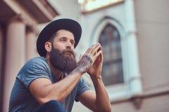 Un varón hermoso del inconformista con una barba elegante con un tatuaje en hola foto de archivo