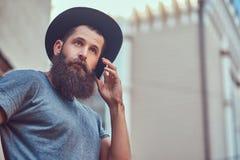 Un varón hermoso del inconformista con una barba elegante y tatuaje en el suyo a imagenes de archivo