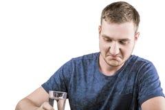 Un varón infeliz en una camiseta azul marino está tomando las píldoras de la medicina, aisladas en un fondo blanco Fotografía de archivo