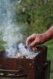 Un varón lleva a cabo el pedazo de madera bajo inflamación para comenzar un fuego del campo Imágenes de archivo libres de regalías