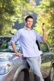 Un varón sonriente que lleva a cabo un clave del coche Foto de archivo libre de regalías