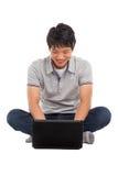 Un varón sonriente que trabaja en una computadora portátil Fotografía de archivo