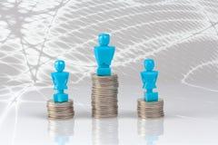 Un varón y dos estatuillas femeninas que se colocan en pilas de monedas Imágenes de archivo libres de regalías