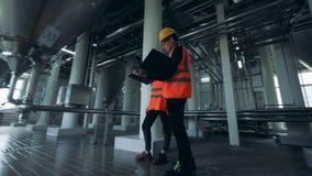Un varón y los ingenieros de sexo femenino está observando una instalación de la destilería metrajes