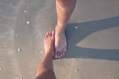 Un varón y un pies femeninos en la arena imagen de archivo libre de regalías