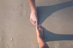 Un varón y un pies femeninos en la arena fotografía de archivo