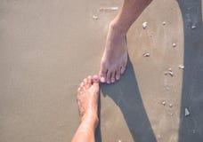 Un varón y un pies femeninos en la arena imagenes de archivo
