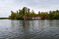 Un varadero con un tejado rojo en la orilla del lago imagenes de archivo