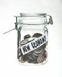 Un vaso d'inscatolamento ha riempito di monete Immagine Stock
