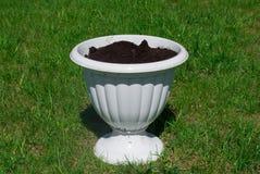 Un vaso da fiori bianco con terra nera Immagini Stock