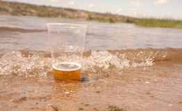 Un vaso de cerveza en el agua imagen de archivo libre de regalías