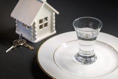 Un vaso de medida de vodka en una placa blanca contra el contexto de una casa miniatura y las llaves en un fondo negro Fotografía de archivo