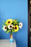 Un vaso dei girasoli e del fondo blu immagine stock libera da diritti
