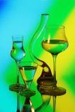 Un vaso di vetro e tre bicchieri di vino Fotografia Stock Libera da Diritti