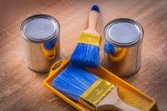Un vassoio di due della pittura spazzole delle latte sul bordo di legno Immagine Stock Libera da Diritti