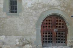 Un vecchie a porta chiusa e finestra di legno con la parete incrinata in vie del villaggio di Lohara in Ludhiana, Punjab immagine stock