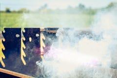 Un vecchio barbecue di cottura a vapore arrugginito quando si accendono nel giardino Immagini Stock Libere da Diritti