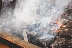 Un vecchio barbecue di cottura a vapore arrugginito quando si accendono nel giardino Immagine Stock
